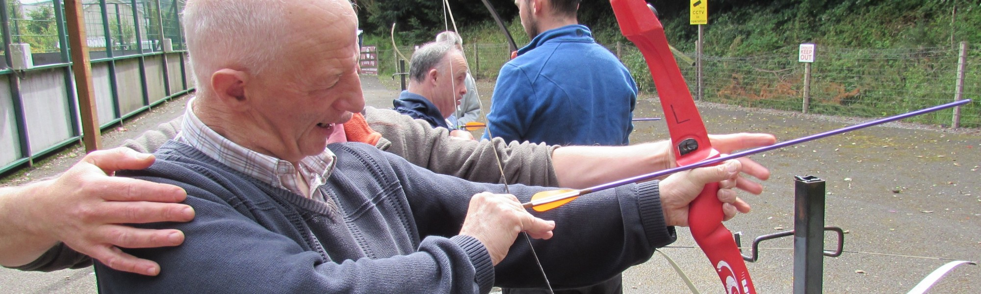 Man being supported to aim and shoot an arrow